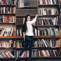 A photo of Veronica getting a book from a big book case.[15]