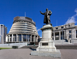 """A statue of                                 Richard Seddon                                , the """"                                 Beehive                                """" (Executive Wing), and                                 Parliament House                                (right), in Parliament Grounds, Wellington."""