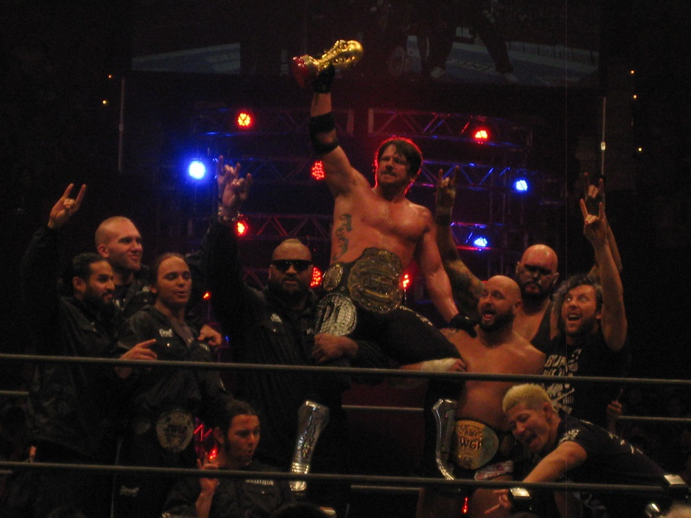 Styles (center - being hoisted) celebrates with Bullet Club after winning the IWGP Heavyweight Championship in February 2015