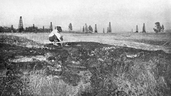 "This photo from Rancho La Brea appeared in the November 9, 1911, Memoirs of the University of California. The caption reads ""The locality at which the principal excavation work of the University of California has been carried on. The exposure to the left shows separation of distinct strata. The small white patches in the asphalt represent weathered bones still in the original matrix. Photograph by Ralph Arnold."""