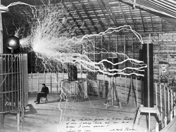 "A multiple exposure picture (one of 68 images created by Century Magazine photographer Dickenson Alley) of Tesla sitting in his Colorado Springs laboratory with his ""magnifying transmitter"" generating millions of volts. The 7-metre (23 ft) long arcs were not part of the normal operation, but only produced for effect by rapidly cycling the power switch."