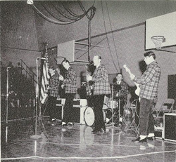 Wilson (second-left) performing with the Beach Boys in Pendleton outfits at a local high school in late 1962