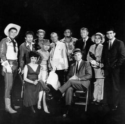 "Guest stars for the premiere episode of                                                   The Dick Powell Show                                  ,                                ""Who Killed Julie Greer?"" Standing, from left: Ronald Reagan,                                 Nick Adams                                ,                                 Lloyd Bridges                                ,                                 Mickey Rooney                                ,                                 Edgar Bergen                                ,                                 Jack Carson                                ,                                 Ralph Bellamy                                ,                                 Kay Thompson                                ,                                 Dean Jones                                . Seated, from left,                                 Carolyn Jones                                and                                 Dick Powell                                ."