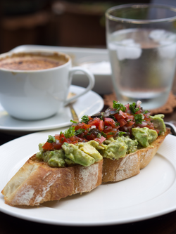 Avocado salad, and a tomato and black olive salsa, on a toasted baguette