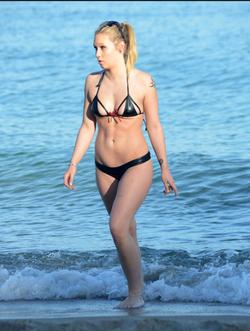 At the beach, in a bikini.
