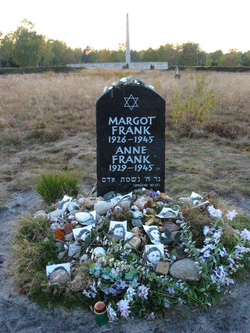 Memorial for Margot and Anne Frank at the former Bergen-Belsen site, along with floral and pictorial tributes