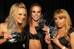 Lexi Belle (right), with Alexis Texas (left) and Tori Black (middle), displaying her trophy backstage at the F.A.M.E. Awards in 2010.