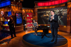 Colbert, in his television series persona, prepares to interview                                 Michelle Obama                                . The set of                                 The Colbert Report                                satirizes cable-personality political talk shows.