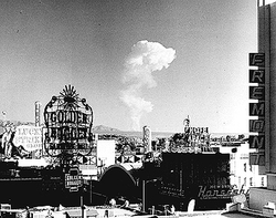 This view of downtown Las Vegas shows a mushroom cloud in the background. Scenes such as this were typical during the 1950s. From 1951 to 1962 the government conducted 100 atmospheric tests at the nearby Nevada Test Site.[2]