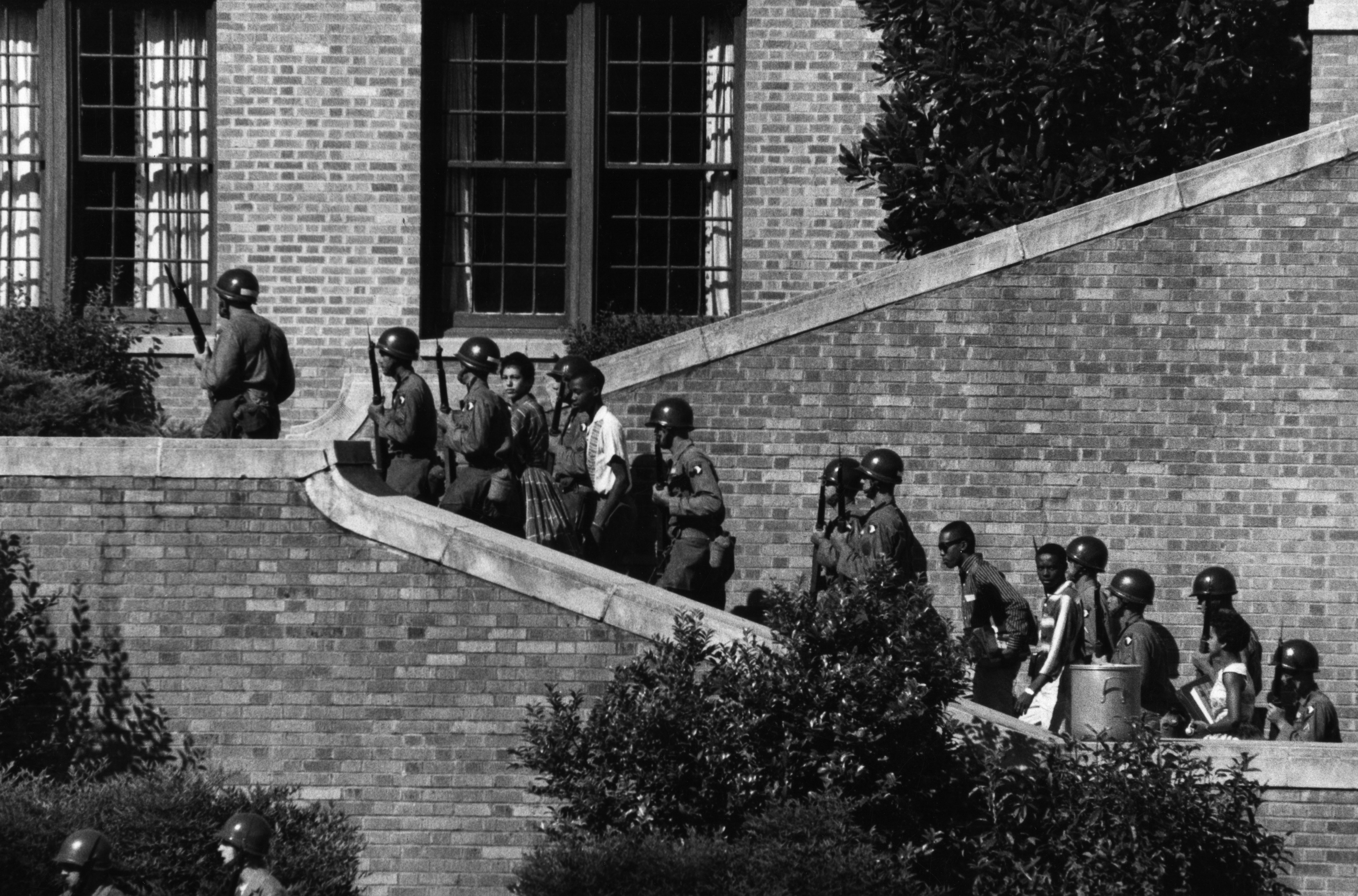 Troops from the 327th Regiment, 101st Airborne escorting the Little Rock Nine African-American students up the steps of Central High.