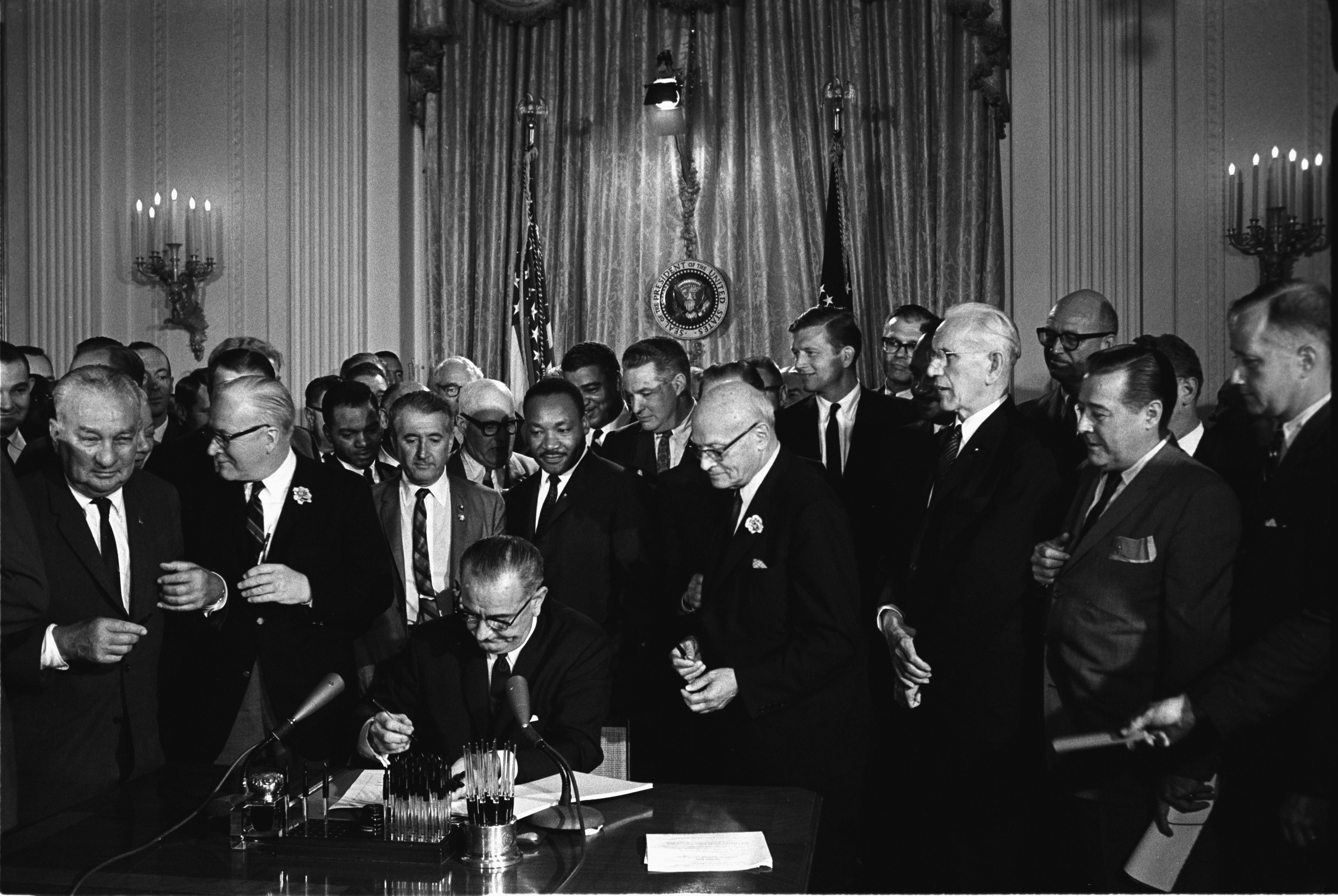 Lyndon B. Johnson signs the historic Civil Rights Act of 1964.
