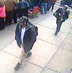 """Tamerlan (front) and Dzhokhar Tsarnaev wearing a Bridgestone hat on security camera footage just prior to the bombing. This and other images released by the FBI taken from other security footage and photos from bystanders would later be considered a """"turning point"""" in the investigation, leading to the subsequent manhunt and capture. [70]"""