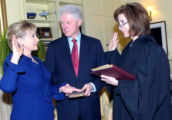 Clinton takes the oath of office as Secretary of State, administered by Associate Judge Kathryn Oberly, as Bill Clinton holds a Bible.