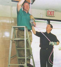 President Bill Clinton installing computer cables with Vice President Al Gore on NetDay at Ygnacio Valley High School in Concord, CA. March 9, 1996.