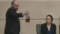 Elliott in court. A prosecutor holding the bottle of alcohol found in her car at the time of the crash.