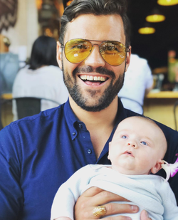 Photo of Alex Tapscott holding a baby.
