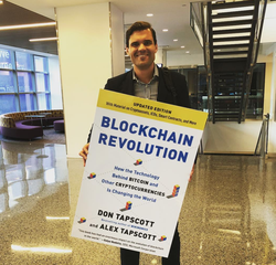 Photo of Alex Tapscott holding a big poster of Blockchain Revolution, his book.