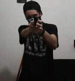 Guilherme Taucci Monteiro Posando com uma arma