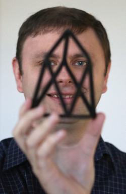 Dan Larimer holds a 3D-printed chestahedron, the geometric shape that serves as a logo for block.one. The company has donated $3 million to Virginia Tech. MATT GENTRY | The Roanoke Times