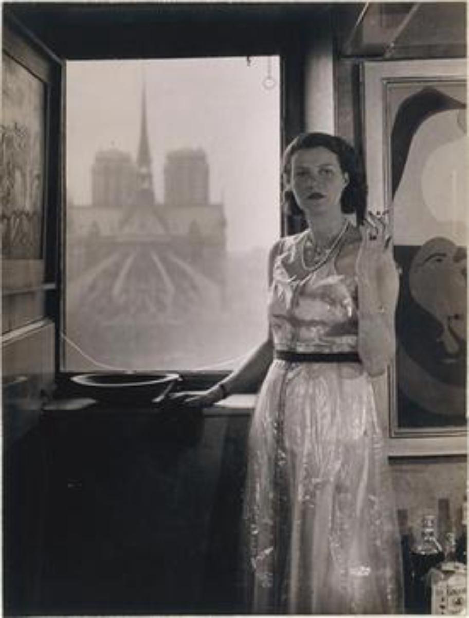 """Peggy Guggenheim, c.1930, Paris, photograph Rogi André (Rozsa Klein). In the background, <a href=""""/content/Notre_Dame_de_Paris"""" style=""""color:blue"""">Notre Dame de Paris</a>, and on the right, <a href=""""/content/Joan_Mir%C3%B3"""" style=""""color:blue"""">Joan Miró</a>, <i>Dutch Interior II</i> (1928)."""